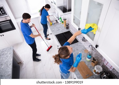 Group Of Young Janitors In Uniform Cleaning Kitchen At Home