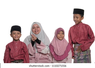 A group of young malay muslim male and female children/teenagers wearing traditional malay costumes isolated on white background