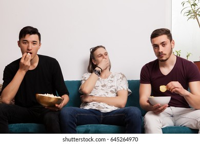 Group of young male friends looking at the ball game and in the camera