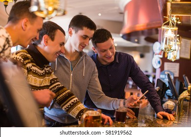 Group of young male friends in the pub. Guys look on the phone and laughing