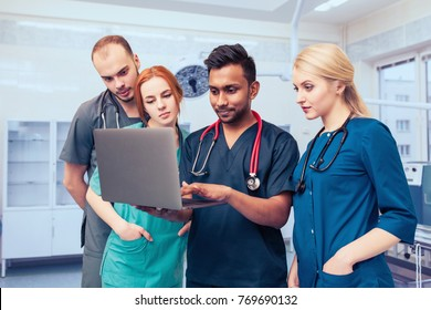 A group of young medical students with mixed-race surgeons examining these operations in a laptop.