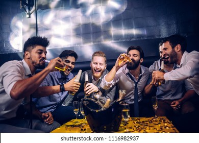 Group of young men drinking beer at a nightclub