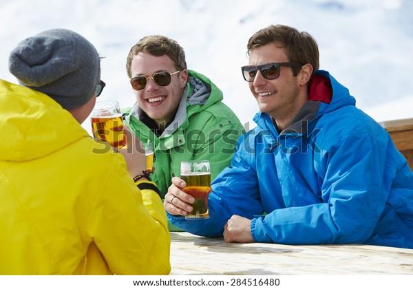 Group Of Young Men Enjoying Drink In Bar At Ski Resort