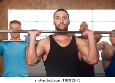 Group of Young Men in Gym Training With Barbells. Small Group of Male Athletes During Workout. Cross Fit Training. Sports, Fitness, Healthy Lifestyle and Teamwork