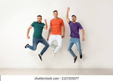 Group of young men in jeans and colorful t-shirts jumping near light wall