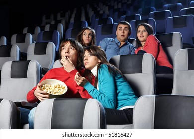 Group of young men look a terrible film at a cinema