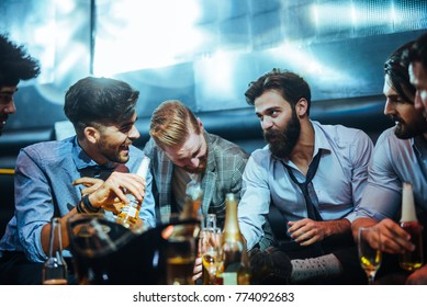 Group of young men talking in a bar, drinking beer