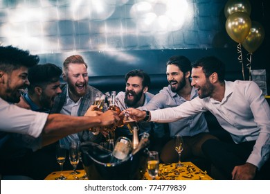Group of young men toasting with beer at a nightclub