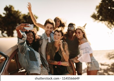 Group of young men and women enjoying on road trip standing by the car and taking selfie. Multiracial group of friends having fun outdoors taking selfie with smart phone.