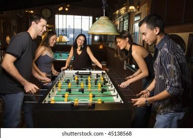 Group of young men and women enjoying a game of foosball in a bar.  Horizontal shot.