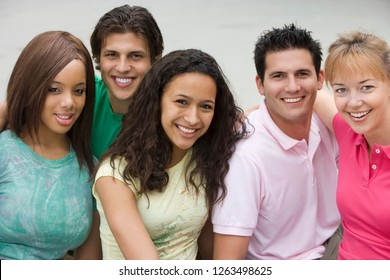 Group of young men and women friends outdoors smiling at camera