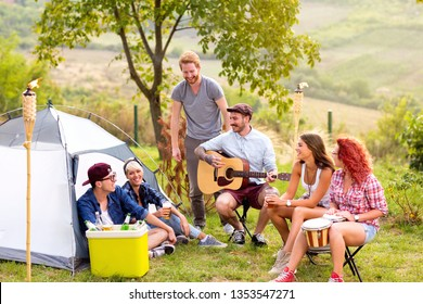 Group of young men and women having fun and playing guitar in nature