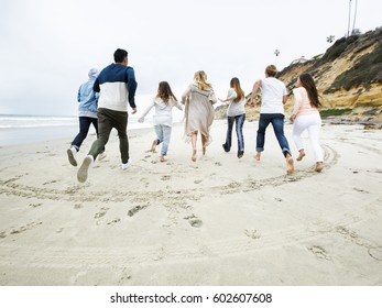 A group of young men and women running on a beach, having fun