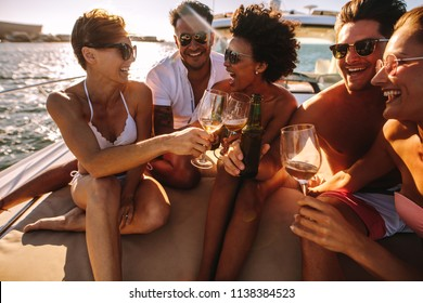 Group of young men and women sitting on the yacht deck and toasting drinks. Young people partying on a boat with drinks.
