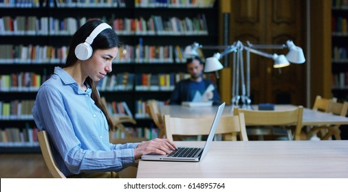 A group of young men and women studying in the library, reading books, or listening to music on the computer in total silence and relaxation. Concept of culture, education, relaxation and study