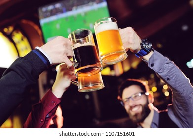 a group of young men's friends in a bar or pub drinking beer with glasses and watching football during the celebration of Oktoberfest