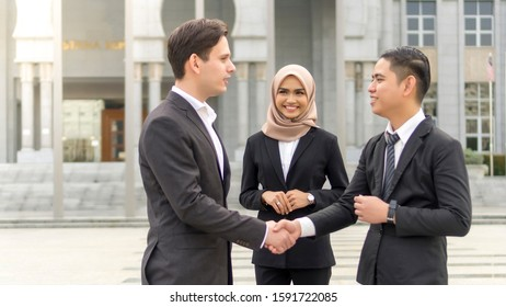 A group of young mixed Asian Executive at the wearing suit handshaking