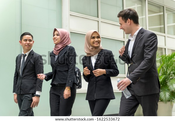 A group of young mixed Asian Executive at the corridor walking and talking to each other