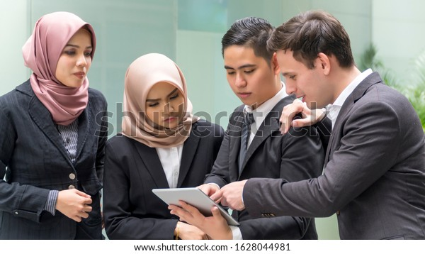 A group of young mixed Asian Executive at the wearing suit holding tablet computer