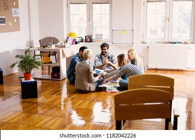 Group of young modern designers sitting on a floor and making new plans.