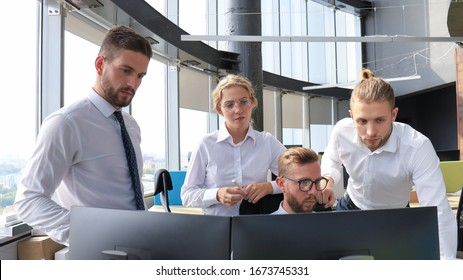 Group of young modern people in formalwear using modern technologies while working in the creative office