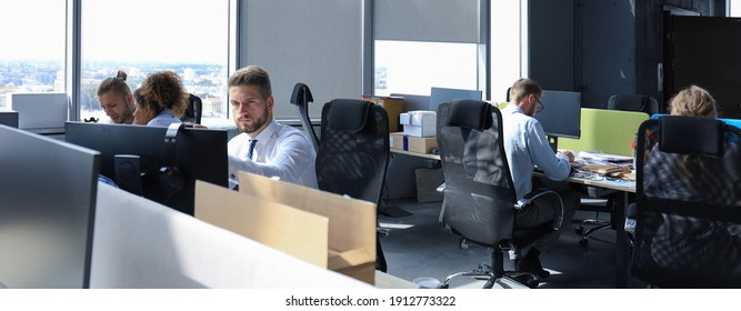 Group of young modern people in formalwear using modern technologies while working in the creative office.