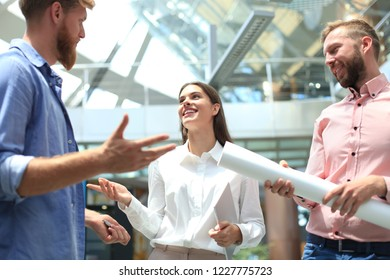 Group of young modern people in smart casual wear standing in creative office.