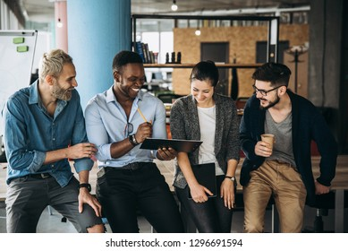 Group of young modern people in smart casual wear smiling and discussing something while working in the creative office