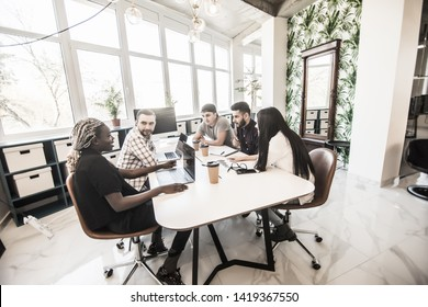 Group of young modern people in smart casual wear discussing something while working in the creative office