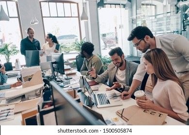 Group of young modern people in smart casual wear communicating and using modern technologies while working in the office