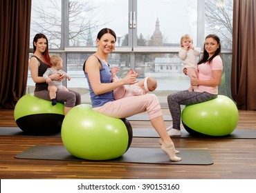 Group of young mothers and their babies doing yoga exercises on gymnastic balls at fitness studio.