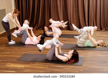 Group of young mothers and their babies doing yoga exercises on rugs at fitness studio.