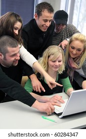 Group of young motivated students looking at a laptop computer
