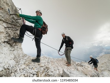group of young mountain climbers on a steep Via Ferrata with a view of the Italian Dolomites