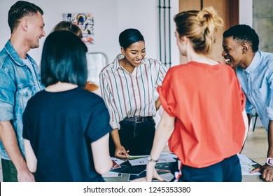 Group of young multicultural people in casual wear laughing during colaboration on design project in modern coworking space.Team of cheerful hipster students having fun during common task