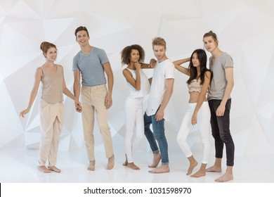 Group of young multi-ethnic beautiful people wearing casual clothes smiling and having fun together against white abstract polygonal background. Asian Caucasian Afro-American attractive stylish men