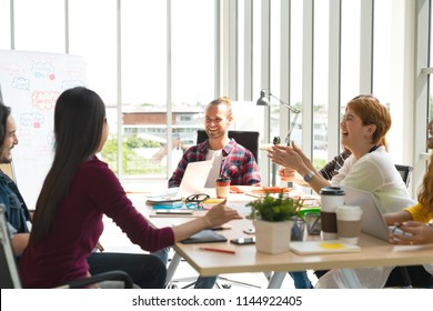 Group of young multiethnic creative team with caucasian man engaged brainstorm in small meeting and talking together in modern office. Casual business with teamwork community discussion concept.