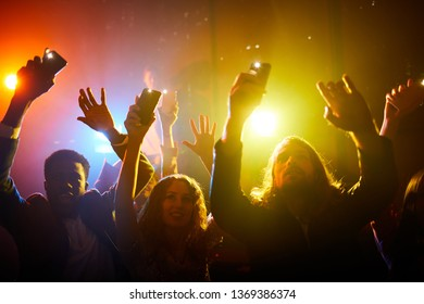 Group of young multiethnic fans waving hands with gadgets and looking at musician while enjoying performance at concert