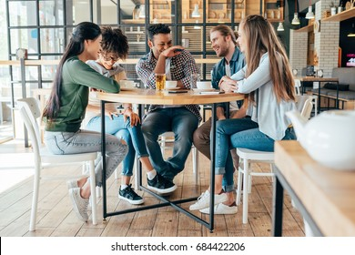 Group of young multiethnic friends spending good time together in cafe
