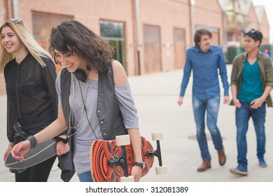 Group of young multiethnic friends walking down the street holding skateboards in their hand, laughing and chatting each other - friendship, amusement, sportive concept