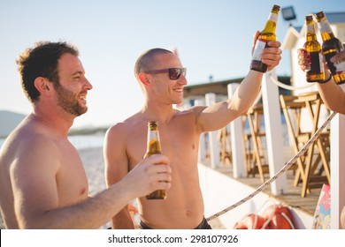 group of young multiethnic friends women and men at the beach in summertime toasting with some beers in a beach bar - friendship, relaxing, happy hour concepts