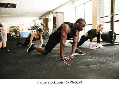 Group of young multiethnic people stretching legs at the gym