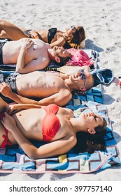 Group of young multiethnic woman and men friends sunbathing on the beach, lying on the sand on their towel - summer, tan, relaxing concept
