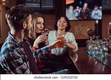 Group of young multiracial friends resting in the pub. Friends sitting at wooden counter and enjoying drinks.