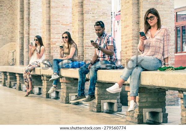 Group of young multiracial friends using smartphone with mutual disinterest towards each other - Technology addiction in actual lifestyle - Soft vintage filtered look with main focus on male person