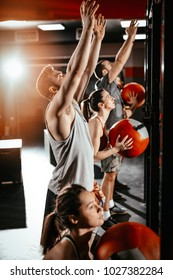 Group of a young muscular friends doing exercise with wall ball at the gym. Selective focus.
