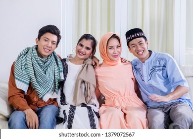 Group of young Muslim community smiling at the camera while sitting together on the couch. Shot at home