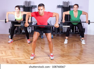 A group of young people in aerobics class doing a dead lift exercise