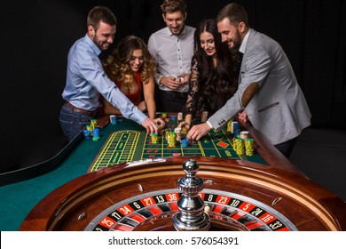 Group of young people behind roulette table