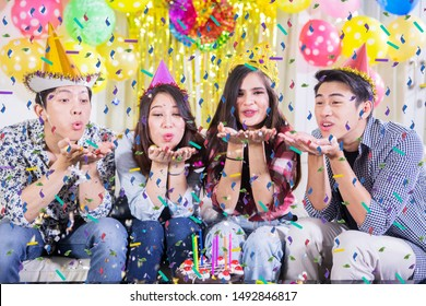 Group of young people blowing colorful confetti from hands during celebrating birthday at home